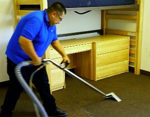 A man in a blue shirt cleaning carpet with vacuum.