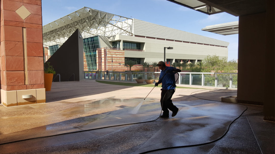 Man using a power washer to clean concrete floor outdoors on a commercial building.