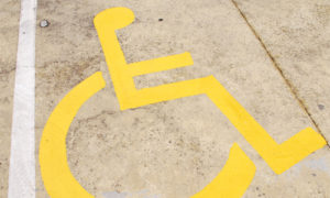 Handicapped parking space icon painted in yellow on concrete.