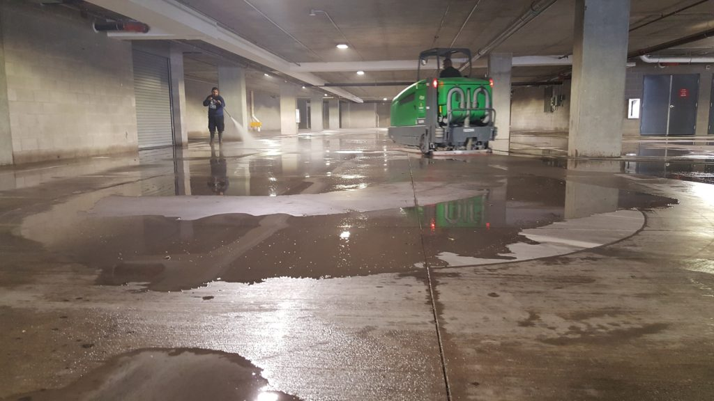 green parking garage sweeper cleaning a parking garage