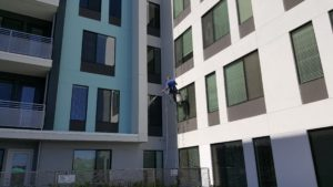 man rappelling from a building and power washing a windowsill
